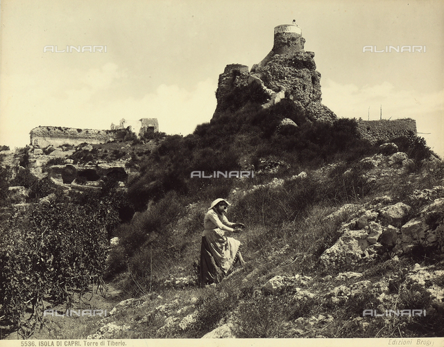 View of the Tower of Tiberius in Capri. In the foreground is a woman in traditional dress.