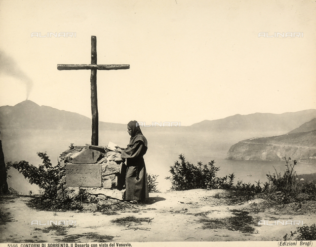 A frair in prayer in front of a cross overlooking the sea in the Sorrento countryside. Vesuvius is in the background.