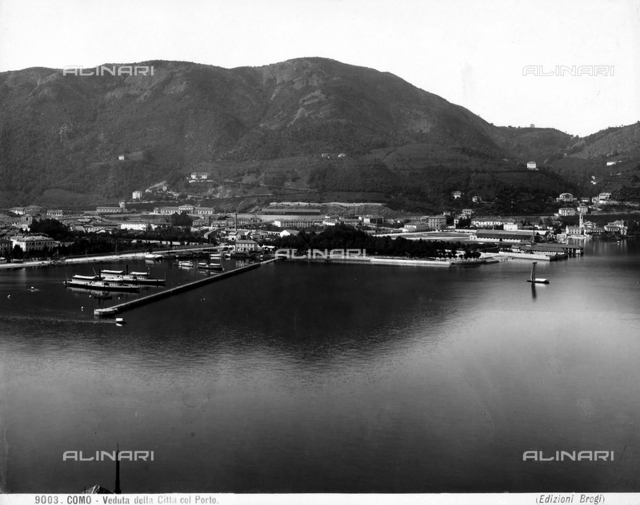 View of Como's harbor with some docked ships and homes of the city of Como in the background.