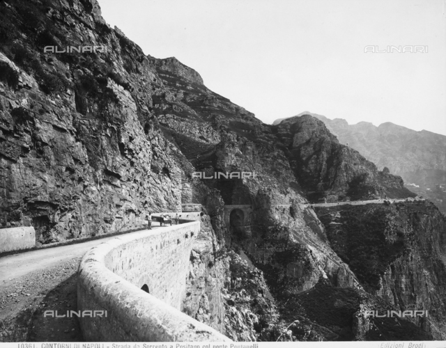 A stretch of road that leads from Sorrento to Positano with the Pontanelli Brisge. The road is occupied by two men with a cart.