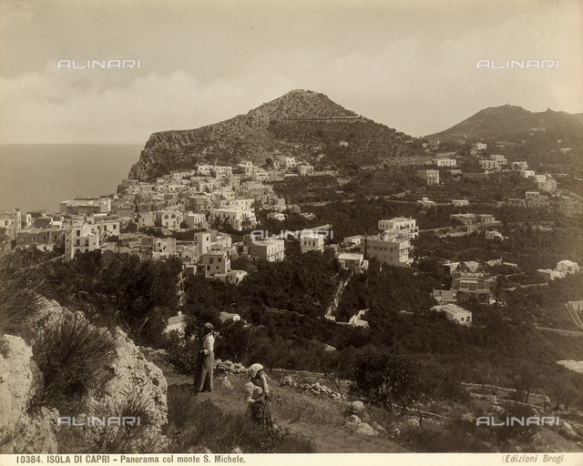 View of the Isle of Capri with Mount San Michele and two figures in the foreground.