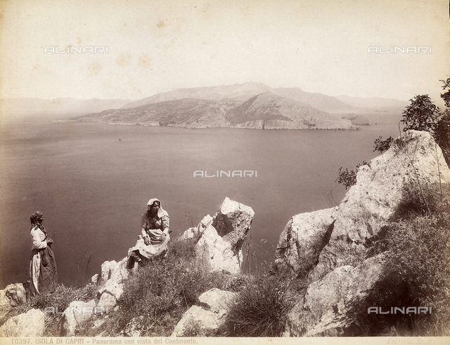 View of the Isle of Capri with two women sitting on rocks in the foreground.