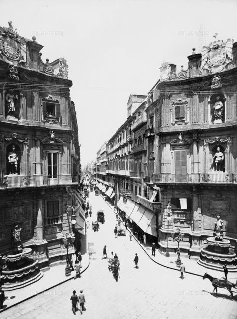 Pedestrians and carriages on Via Maqueda, in Palermo, that ends in Piazza dei Quattro Canti