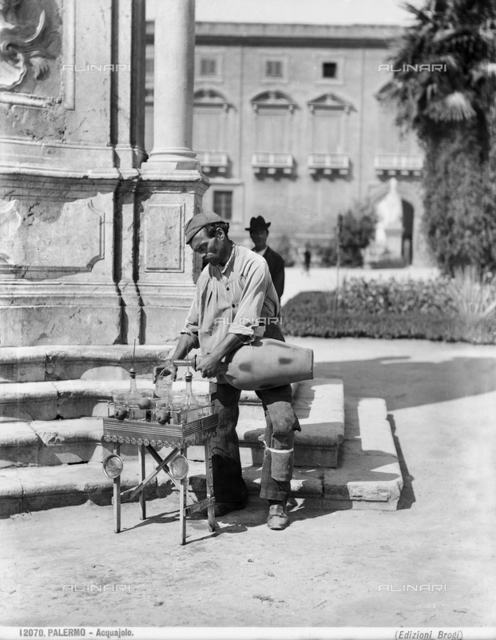 A water-vendor of Palermo pours some water in a glass.