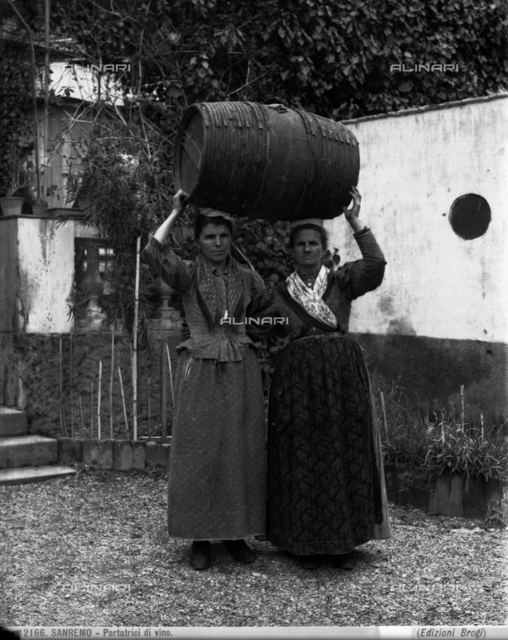Two women bearing a wine cask on their heads in San Remo.