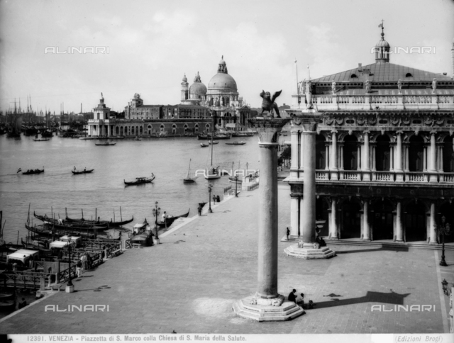 View of the lagoon from Piazzetta, S. Marco, Venice. Two monolithic columns topped by a statue of the Lion of St. Mark and St. Theodor and the Church of S. Maria della Salute.