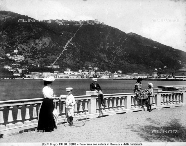 View of Lake Como with the town Brunate above. In the foreground is a woman and children dressed in elegant twentieth century clothing.