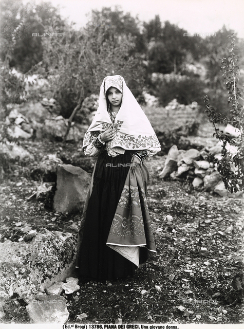 A young woman in traditional dress photographed at Piana dei Greci, today's Piana degli Albanesi, in the province of Palermo