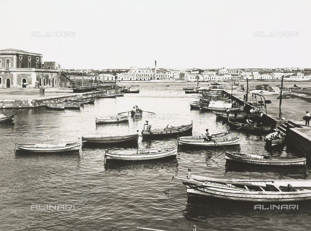 View of the port of Syracuse; several boats are moored near the pier