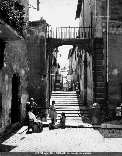 Busy view of some girls and a woman sitting on a road with steps in Toscanella, Dozza