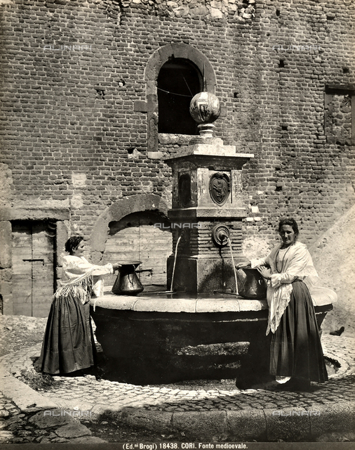 Two women dressed in traditional clothing fill up their pitchers at the fountain in Cori.
