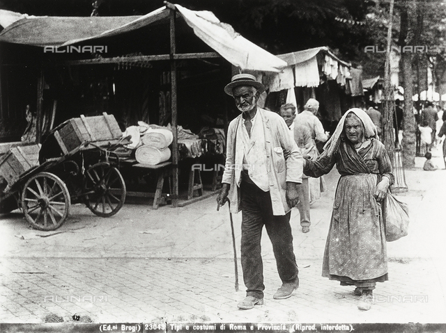A couple of old people in Rome walking along the streets with stalls set up for the market.