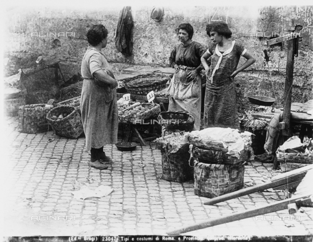 Three women next to some baskets with their merchandise in Rome.