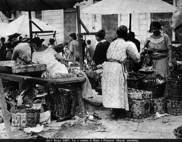 View of a city street characteristic of Rome and its outskirts. The image shows some market stands with vendors and clients. A few women are busy choosing merchandise. A vendor is weighing vegetables.