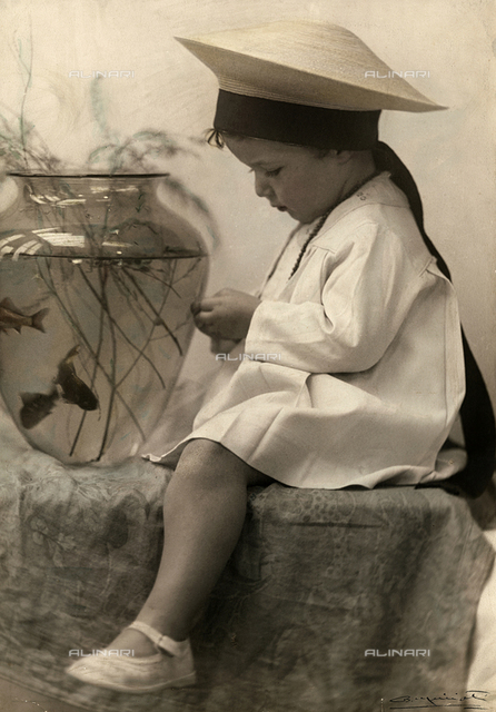 Portrait of a little girl, sitting in front of a vase with goldfish