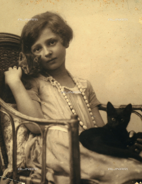 Portrait of a baby sitting on a seat with two little cats