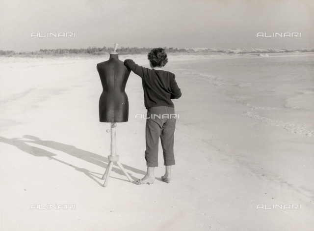 Woman with manikin on the beach