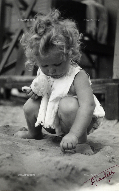 A baby girl playing with sand. Postcard sent by the photographer to Vincenzo Balocchi