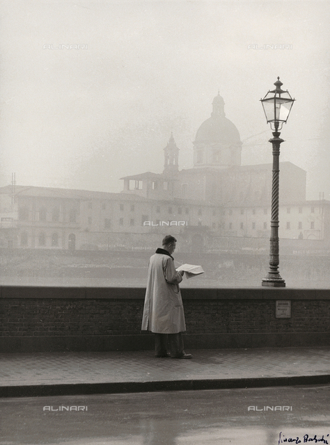A man reading a newspaper while walking along Lungarno Amerigo Vespucci in Florence; in the background the Church of the Cestello