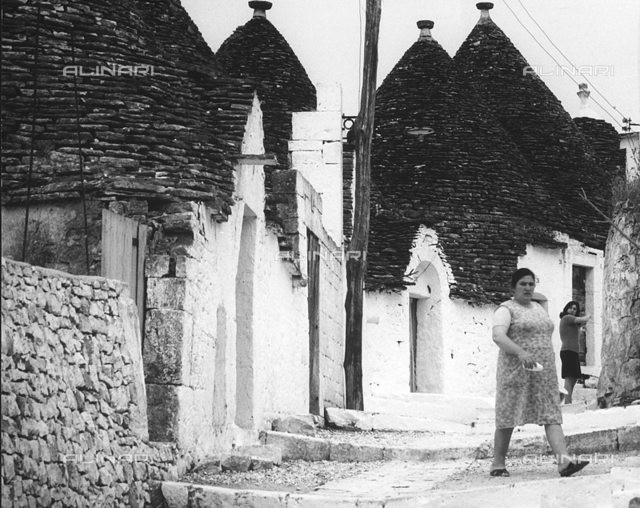 """Alberobello"". View of an alley in Alberobello; the photograph shows two women walking on the street of the town."