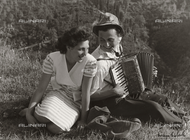 """Words of Love"". A young couple in love sitting in a field smiling. The man is playing an accordion."