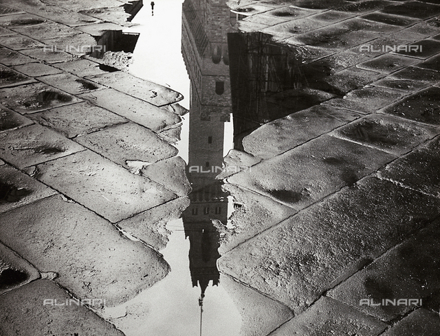 The bell tower of Palazzo Vecchio in Florence reflected in a puddle