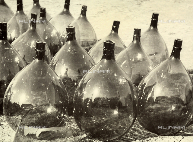 """""""Demijohns'. Demijohns placed on the ground in a series of rows."""