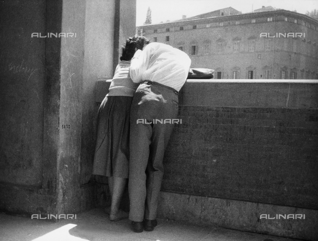 """Love in Florence"". A young couple, with their backs to the camera, in an affectionate embrace on the Lungamo in Florence."