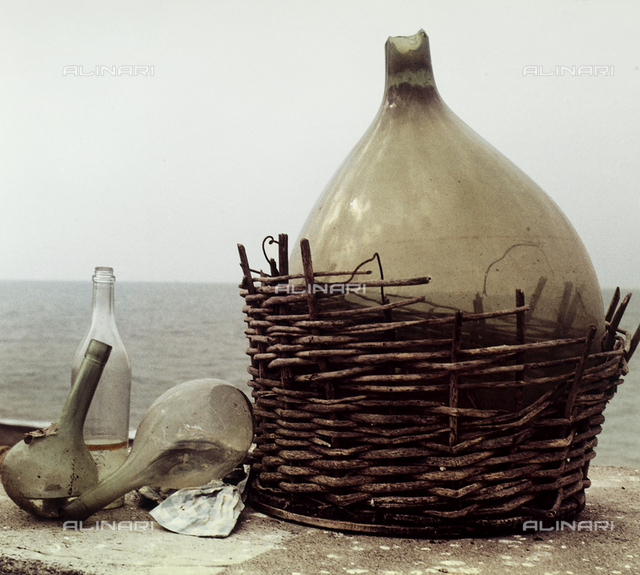 Demijohn and glass flasks left on the seashore.
