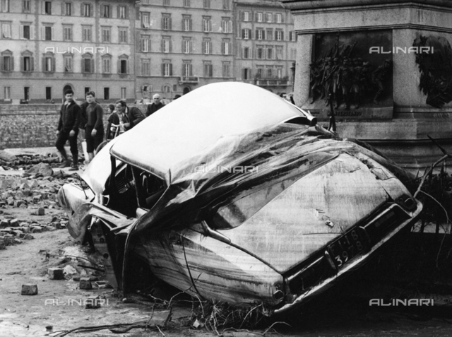 Automobile destroyed and flung up against a monument by the force of the water, during the flood in Florence