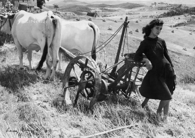 """""""Colli senesi"""", portrait of young woman leaning against a plow"""
