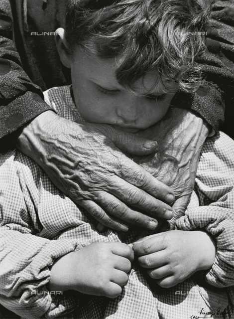 Portrait of a child dressed in a preschool pinafore with the hands of an elderly woman draped across his chest.