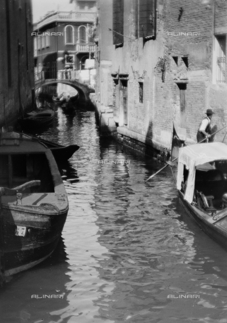 Boats and gondolas in a canal of Venice