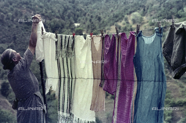 Old woman hanging clothes