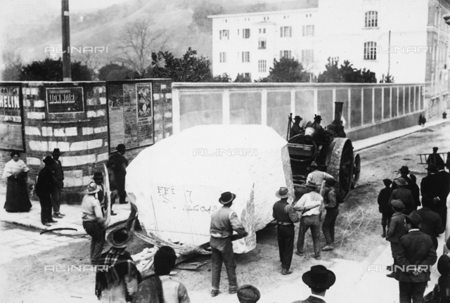 A steam locomotive, called the 'ciabattona' (shuffler), along a road in Carrara transports a block of marble destined for a sculptor's studio
