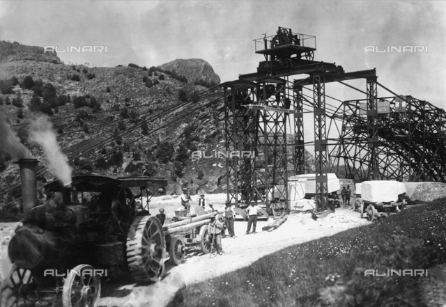 "Several excavators in the Apuan Alps are in the process of loading the blocks of marble onto the car of a steam locomotive, or 'ciabattona"" (shuffler), that will transport them to the valley"
