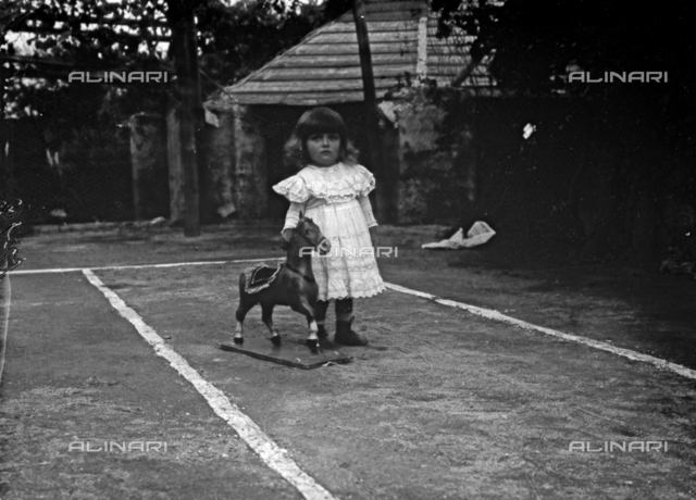 Portrait of little girl with his rocking horse