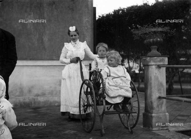 Nurse carrying two children in a wheelchair in the district of Catania Canalicchio