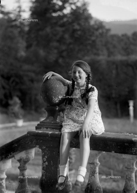 Ritratto di bambina seduta su una balaustra