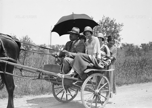 Couple on a cart along a street in the countryside, Castelnuovo