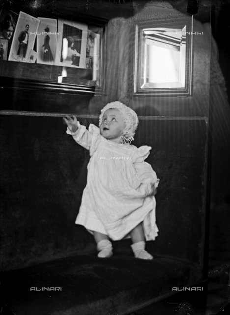 Portrait of baby standing on a couch; above him, some photographs hanging on the wall