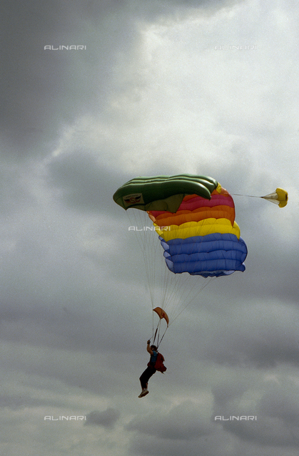Parachutists during a jump. In the background the sky lined by clouds