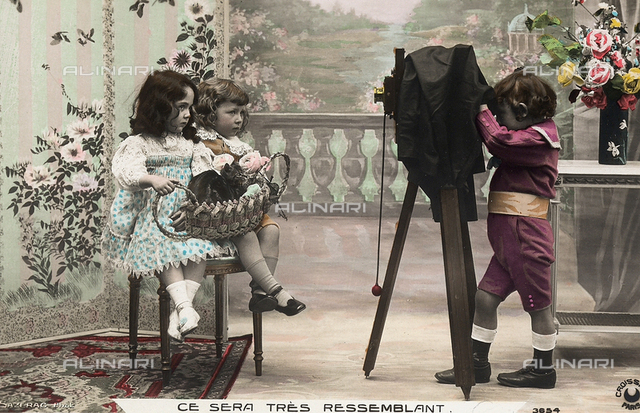 A charming scene depicting a very young photographer, taking a picture of two children with his tripod mounted camera