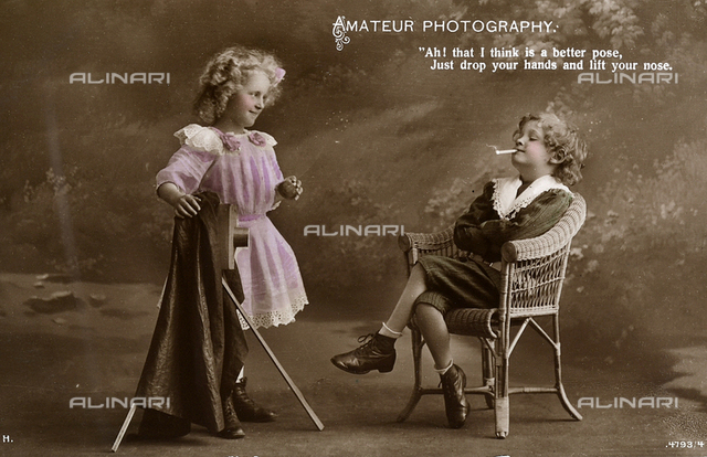 A boy sitting in a chair, arms folded and cigarette in mouth, takes directions on how to pose from a very young female photographer