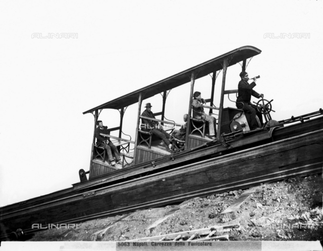 Vesuvian funicular car moving on the track with five passengers on board, including the car operator