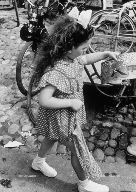 """In a hurry"". A little girl on a street as she passes by a few parked bicycles"
