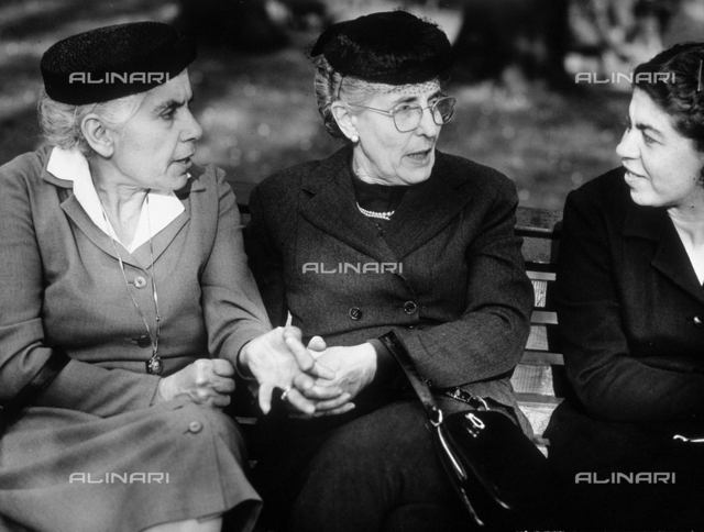 Three women seated on a bench, talking