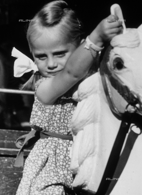 Portrait of a little girl on a merry-go-round horse