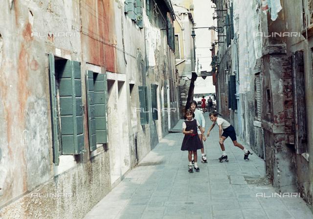 Children on roller skates in a street in Venice