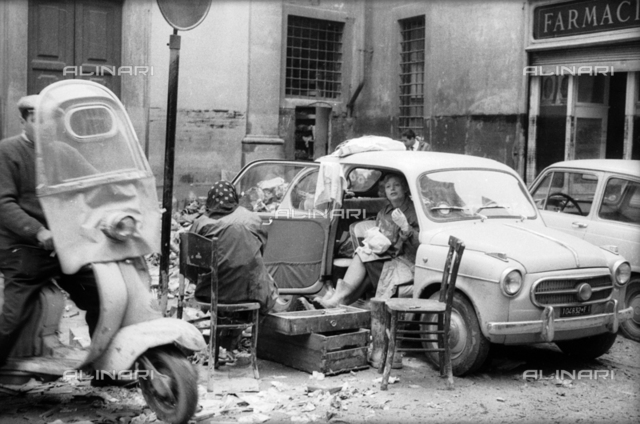 Florence flood of November 4, 1966: Women with a car in  the square of Santa Maria in Campo